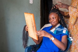 Beautiful African girl at local home salon braiding her hair and admiring face through wooden made mirror