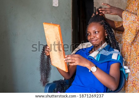 Beautiful African girl at local home salon braiding her hair and admiring face through wooden made mirror Stock photo ©