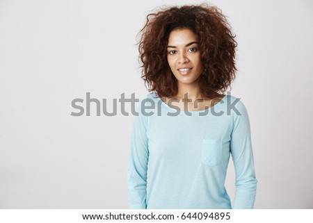 Beautiful african girl in blue shirt smiling looking at camera.