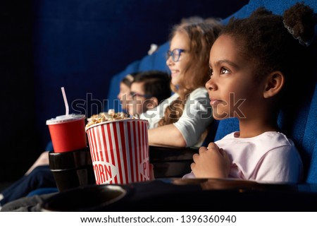 Beautiful african girl with funny hairstyle watching excited movie in cinema. Wonderful little child sitting with friends, eating popcorn and smiling. Concept of entertainment and enjoyment.