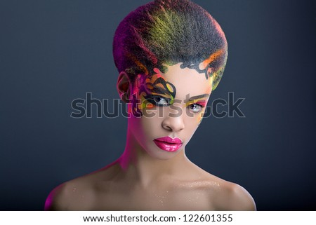 Beautiful african girl with neon make up on dark blue background