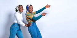 Beautiful African millenial Muslim twins feeling happy and pointing to a copy space-concept on moslem identical twins and commercial advertisement