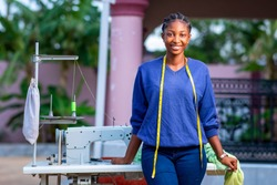 Beautiful African seamstress standing in front of sewing machine with measuring tape around neck,cheerfully looking at camera-concept on millennial black female entrepreneurship