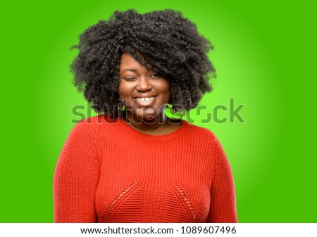 Beautiful african woman blinking eyes with happy gesture