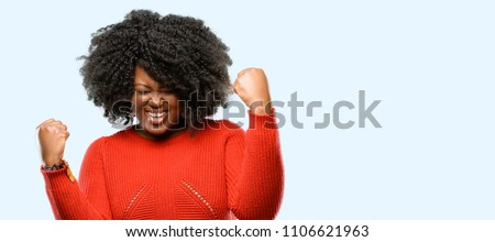 Beautiful african woman happy and excited expressing winning gesture. Successful and celebrating victory, triumphant, blue background