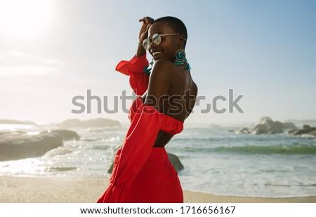 Beautiful african woman in red dress enjoying on the beach. Smiling female in beautiful dress walking along the shore.