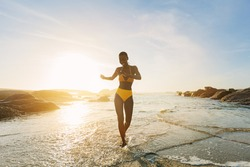 Beautiful african woman in yellow bikini dancing and enjoying on the beach. Smiling female in swimwear coming out of the sea at sunset.