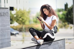 Beautiful African woman listening to music with earphones and smart phone outdoors. Arab girl in sport clothes with curly hairstyle in urban background.