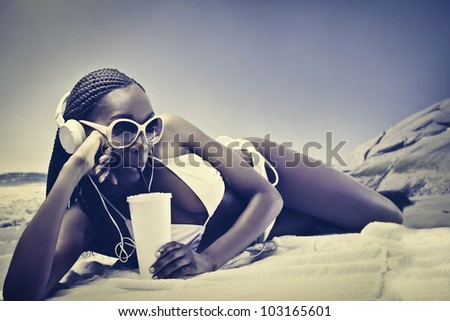 Beautiful african woman lying on a beach and having a refreshing drink