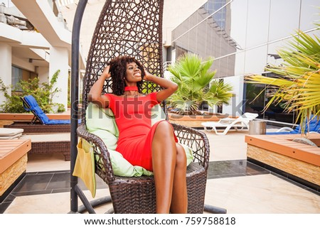 Beautiful African woman sitting on a hanging chair
