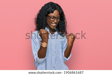 Beautiful african young woman wearing casual clothes and glasses celebrating surprised and amazed for success with arms raised and eyes closed. winner concept.  Photo stock ©