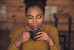 Beautiful Afro American girl in casual clothes is smelling coffee and smiling while resting in cafe