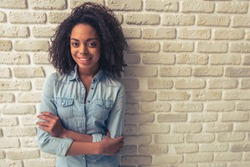 Beautiful Afro American girl is looking at camera and smiling while standing with crossed arms against white brick wall