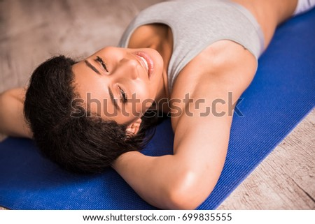 Beautiful Afro American sports girl is smiling while lying on yoga mat at home