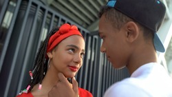 Beautiful afro-american teen couple attempting to kiss, romantic feelings
