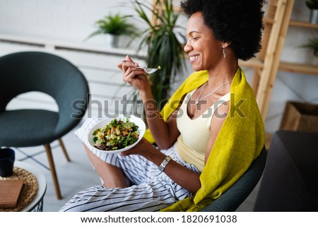 Beautiful afro american woman eating vegetable salad at home.