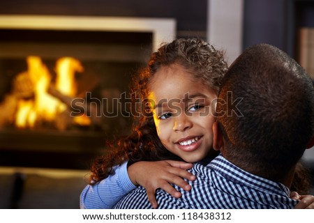 Beautiful afro little girl hugging father at home by fireplace, smiling.