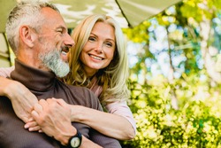 Beautiful aged blond woman hugging her grey-haired husband in park