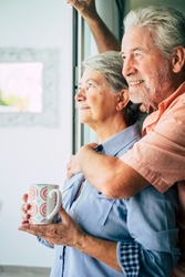 beautiful aged caucasian couple man and woman looking outside the window at home ina romantic moment of the day. foreverness life concept for caucasian happy people together hugging