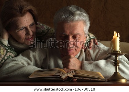 Beautiful aged couple sitting at a table on a brown background