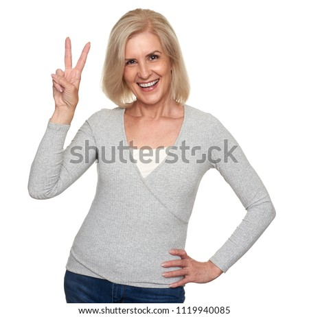 Beautiful aged woman is showing peace sign and smiling. Old lady looking at the camera playfully. Isolated on gray background