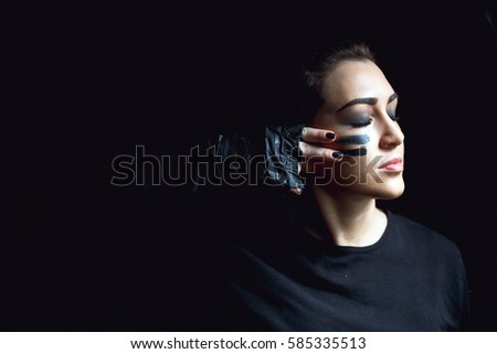 Beautiful aggressive woman over dark background. Dark and mysterious a pretty girl stands in shadow with camoflauge paint on her face.
