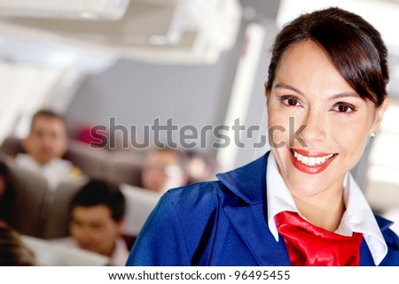 Beautiful air stewardess in an airplane cabin smiling