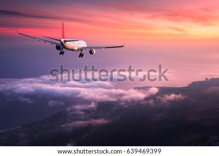 Beautiful airplane. Landscape with big white passenger airplane is flying in the red sky over the clouds at colorful sunset. Journey. Passenger airliner is landing. Business trip. Commercial aircraft