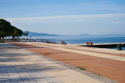 Beautiful alley  and benches along shore. Empty beach promenade.