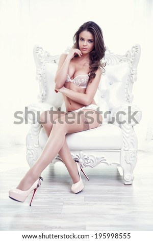 Beautiful alluring young woman in sexy white lingerie sitting in luxury armchair