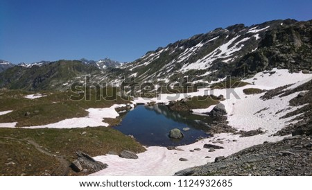 Beautiful Alpine glacier lake on the slopes of Val de bagnes near Corbassière Glacier on a picturesque blue Summer day - Valais - Switzerland