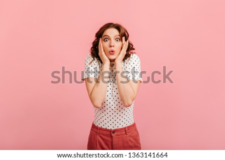 Beautiful amazed girl in t-shirt looking at camera. Studio shot of charming surprised lady isolated on pink background.