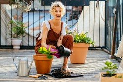Beautiful amazing blond romantic woman among flowers at her balcony during planting. People, gardening, planting and profession concept. Gardener planting banana tree to flower pot on terrace at home.