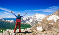 Beautiful amazing day summer mountains. A woman goes a sport hike in holidays. Nature background. Northern country Russia Caucasus wilderness. Rocky route. Blue sky. Inspiring leisure