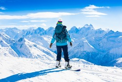 Beautiful amazing day winter mountains. A woman rides snowboard. Sport hike in holidays. Landscape inspiring. Cool fun girl. Blue sky and white snow. Happy hobby, blue jacket