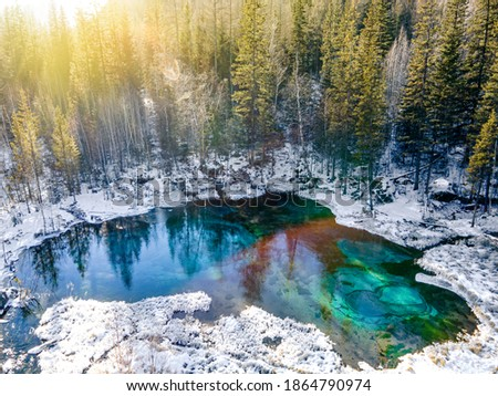 Photo of  Beautiful amazing landscape of a mountain ice-free lake surrounded by a winter forest. Geyser lake is a famous attraction of the Altai mountains. Siberia, Russia. top view, aerial view,