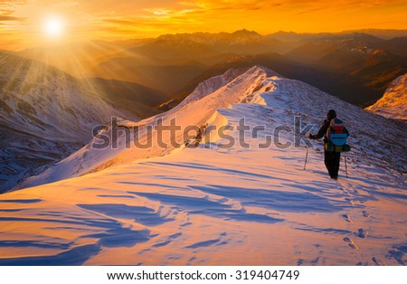 Beautiful amazing sunset winter mountains.  A man goes a sport hike in snow holidays. Christmas background. Unique landscape. Northern country Russia Caucasus. Quest