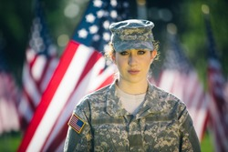 Beautiful American soldier looking into the camera. American flags as background