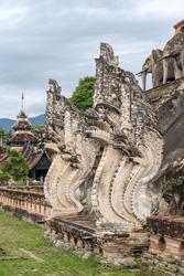 Beautiful ancient stucco naga and elephant decor on main stupa at Wat Chedi Luang buddhist temple, famous landmark of Chiang Mai, Thailand