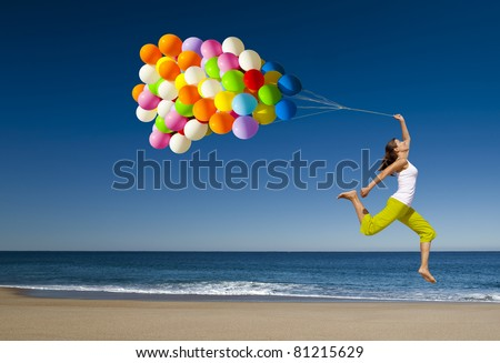 Beautiful and athletic girl with colorful balloons jumping on the beach #81215629