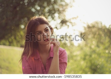 Beautiful and attractive woman landscape portrait watching at something, wearing a pink shirt and multiple gold rings