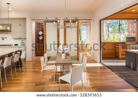 Beautiful and Bright Dining Room Interior, Kitchen, and Outdoor Patio in New Luxury Home
