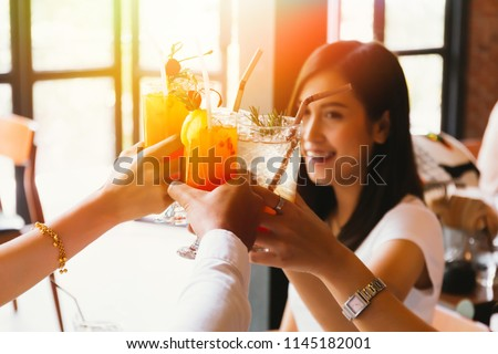 Beautiful and cheerful Asian woman cheering up for toast and celebration with friends in bar - focus on glasses #1145182001