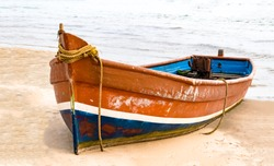 Beautiful and colorful small Fishing Canoe beached up on coastal island. This fishing canoe is generator powered and is used for fishing in high seas, and in offseason, to transport and ferry tourists