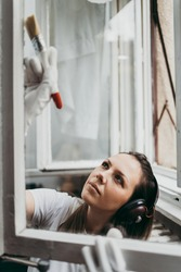 Beautiful and diligent middle age handy woman renovating her old home or apartment. She is holding professional paintbrush and painting windows. Do it yourself housework concept.