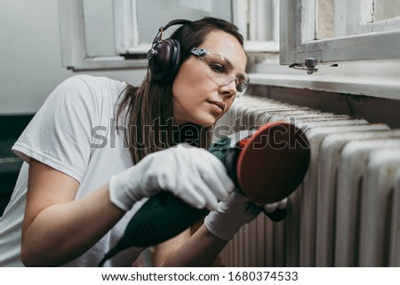 Beautiful and diligent middle age handy woman renovating her old home or apartment. She is holding professional grinder and brushing radiator for later painting. Do it yourself housework concept. Photo stock ©