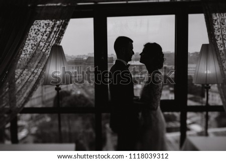 beautiful and elegant blonde bride in a long white dress with her handsome bride in a blue suit standing in the hotel room near window #1118039312