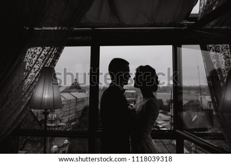 beautiful and elegant blonde bride in a long white dress with her handsome bride in a blue suit standing in the hotel room near window #1118039318