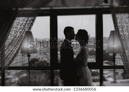 beautiful and elegant blonde bride in a long white dress with her handsome bride in a blue suit standing in the hotel room near window #1336680056
