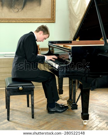 Beautiful and elegant young pianist plays black grand piano